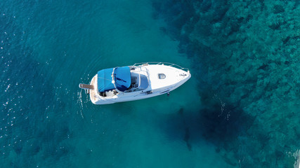 Aerial bird's eye view photo taken by drone of boat cruising in caribbean tropical beach with turquoise - sapphire waters