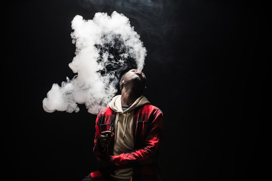 Young african man on a black background holding an electronic cigarette, vaping device, mod, e-cig isolated on black background