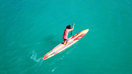 Aerial drone bird's eye view of young man exercising sup board in turquoise tropical clear waters
