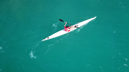 Aerial drone bird's eye view of sport kayak operated a young men in tropical exotic turquoise clear ocean
