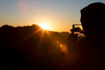A man or woman takes a photo of a beautiful sunrise on his phone. Siluet.