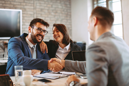 Young business couple make a deal and shake hands
