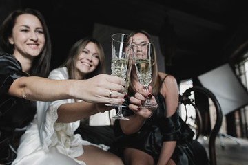 Three happy women sitting on bed clinking champagne glasses