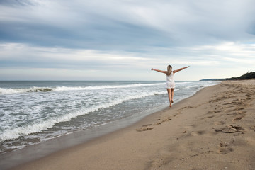 Woman on the beach / Rear view of a beautiful young woman in white dress jumping on the sandy beach