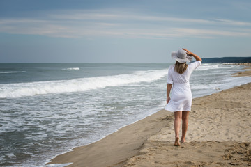 Woman on the beach / Rear view of a beautiful young woman in white dress and summer hat walking on the sandy beach