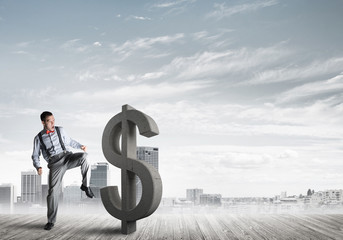 Determined banker man against modern cityscape breaking dollar cement figure