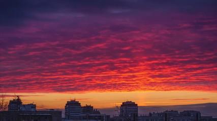 Fotobehang - Light pillar atmospheric effect from sunset sun over epic red clouds and dark city skyline. 4K Timelapse.