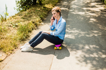 Smiling woman sitting on penny board talking on cell phone