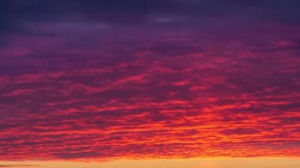 Fotobehang - Light pillar atmospheric effect from sunset sun over epic red clouds. Zoom in on dark city skyline. 4K UHD Timelapse.