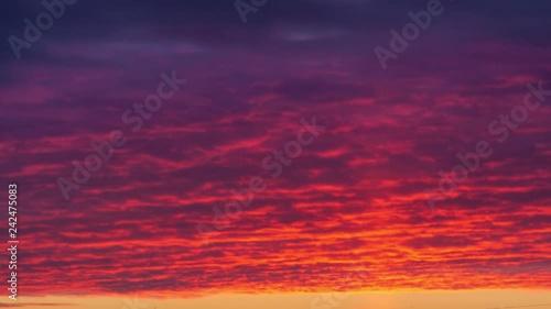 Fotobehang Light pillar atmospheric effect from sunset sun over epic red clouds. Zoom in on dark city skyline. 4K UHD Timelapse.