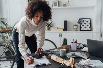 Freelancer standing at her desk, using calculator, taking notes