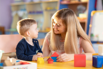Cute woman and little kid boy playing educational toys at kindergarten or nursery room