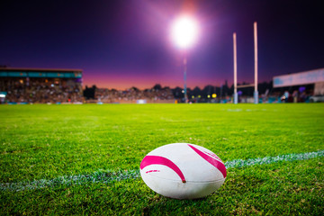 American football, rugby ball on the green grass at the stadium. Professional game in the night. Background sport photo