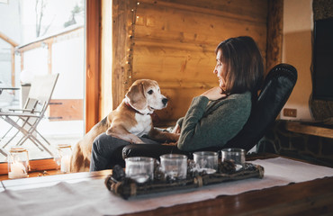 Woman sitting in comfortable chair opposite big window in cozy country home with his beagle dog watching at her. Countryside vacation with pets concept image.