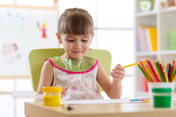 cute child girl cheerfully spending time using color pencils while drawing in playschool