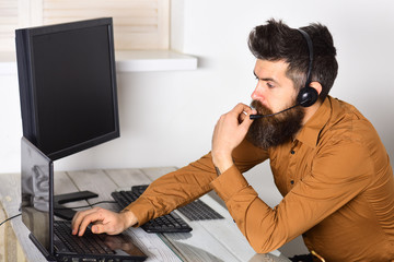 Operator online. Bearded man working in office. Call center operator at work. Man with long beard and headphones. Bearded company representative with laptop. Responding the calls from customers