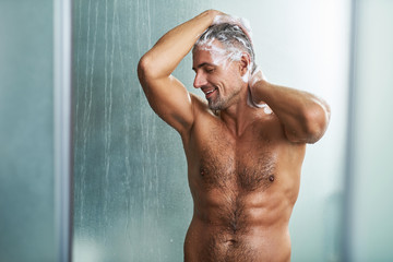 Handsome young man with beautiful muscular body washing his hair
