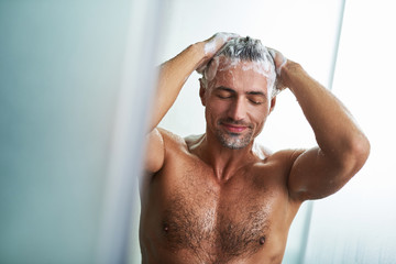 Handsome young man washing hair while taking shower at home