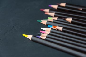 Black colorful pencils on black background.Dark version