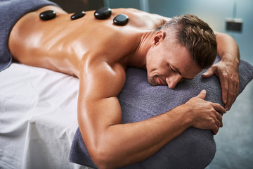 Young man lying on massage table while having spa treatment