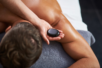 Young man lying on massage table while having hot stone back massage