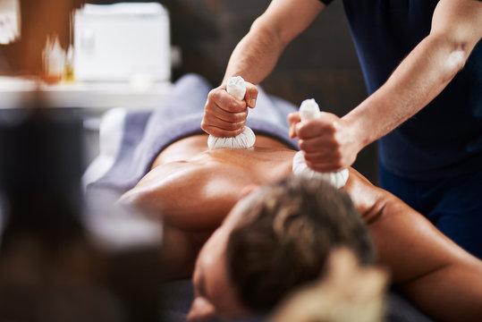 Young man having Ayurveda procedure at wellness center