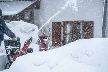 A man cleans snow from sidewalks with snowblower in Bavaria Germany.