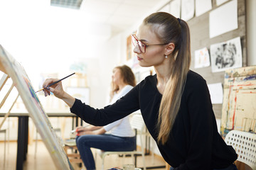 Beautiful fair-haired girl in glasses dressed in black blouse sits at the easel and paints a picture in the art studio