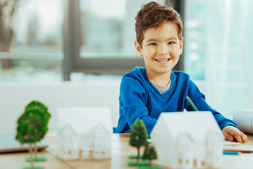 Happy boy smiling while sitting with miniature houses