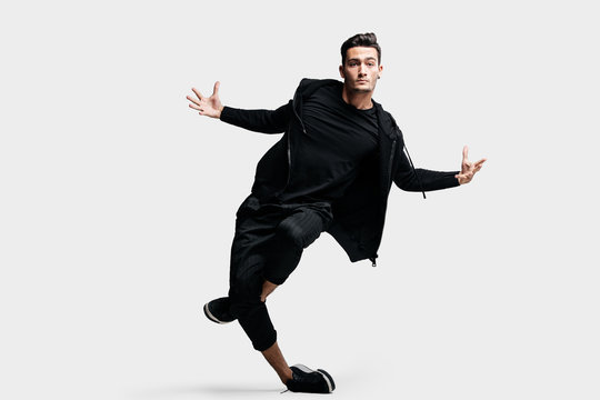 Dark-haired stylish young dancer wearing a black sweatshirt and black pants makes stylized movements of street dances