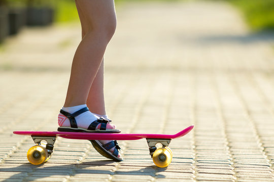 Child slim legs in white socks and black sandals on plastic pink skateboard on bright sunny summer blurred copy space pavement background. Outdoors activities and healthy lifestyle concept.
