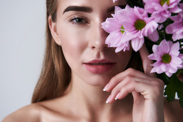 Attractive young woman covering eye with beautiful pink flowers