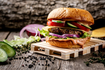 homemade tasty hamburger on wooden pallets. excess weight set. vertical image. menu photo, copy space
