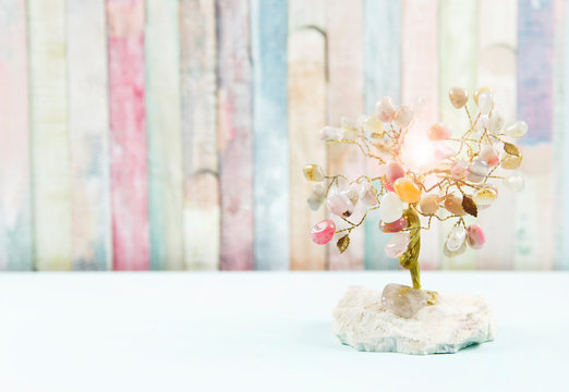 Feng shui gem tree, also called feng shui crystal tree is used for spiritual feng shui cures for love to feng shui for money. Isolated on colorful pastel wooden board background.