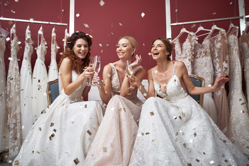 Full length of happy brides with champagne glasses