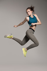 Young active sporty woman dressed in sportswear jumping in studio. Gray background.