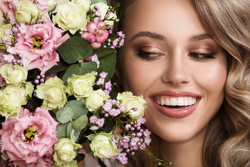 Close up portrait of beautiful smiling woman. Flowers near her face.