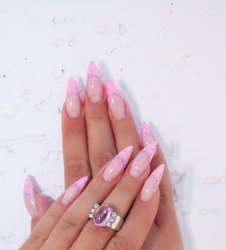 Long French nails with white manicure on a woman's hand.