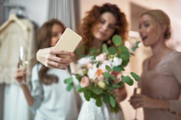 Young ladies making selfie in wedding salon