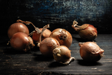 Raw onions lay on a gray table, mint in the background, black background