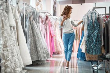 Young lady choosing dress in wedding salon