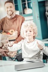 Happy blonde boy demonstrating gold credit card