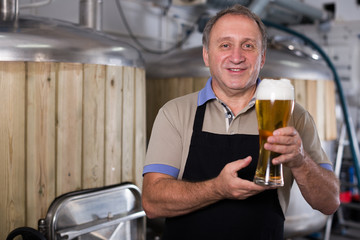 Adult brewer is standing with golden beer in glass