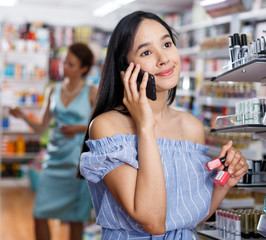 Stylish woman with nail polish talking by phone in store