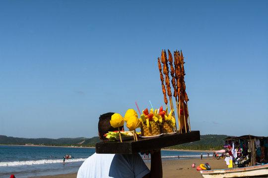 El joven  está vendiendo frutas y camarones en la playa de Manzanillo Colima.
