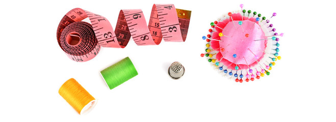 Composition with threads and sewing accessories isolated on white background. Wide photo.