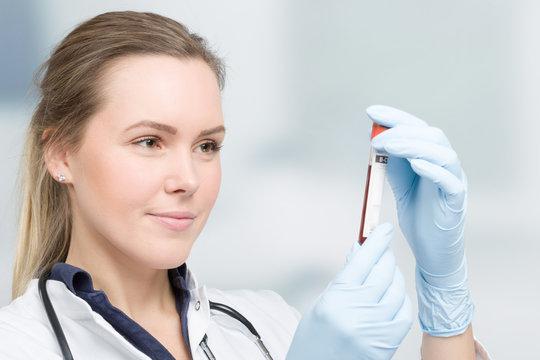 Junge Ärztin mit medizinischen Handschuhen hält eine Blutprobe in der Hand