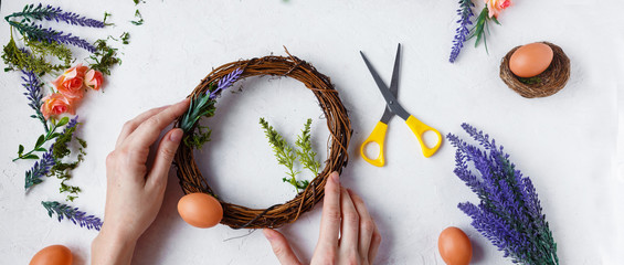 women's hands make an easter wreath of flowers, herbs and eggs on a light background. Easter concept