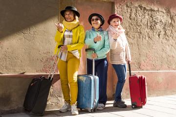 Tre simpatiche amiche di età matura in viaggio con il cappellino e il trolley fanno l'autostop...