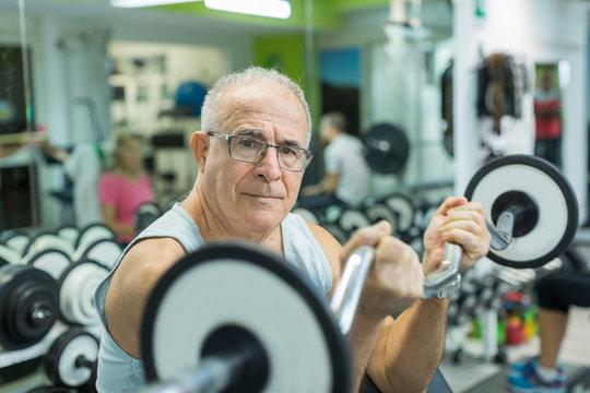 Anziano si allena in palestra con un bilanciere